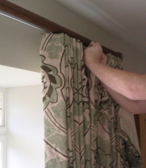 Our expert curtain fitter hanging curtains on a tracked wooden pole