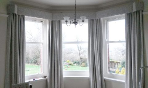 Straight pelmet with pop pom trim in bay window. Morris and Co Pure fabric