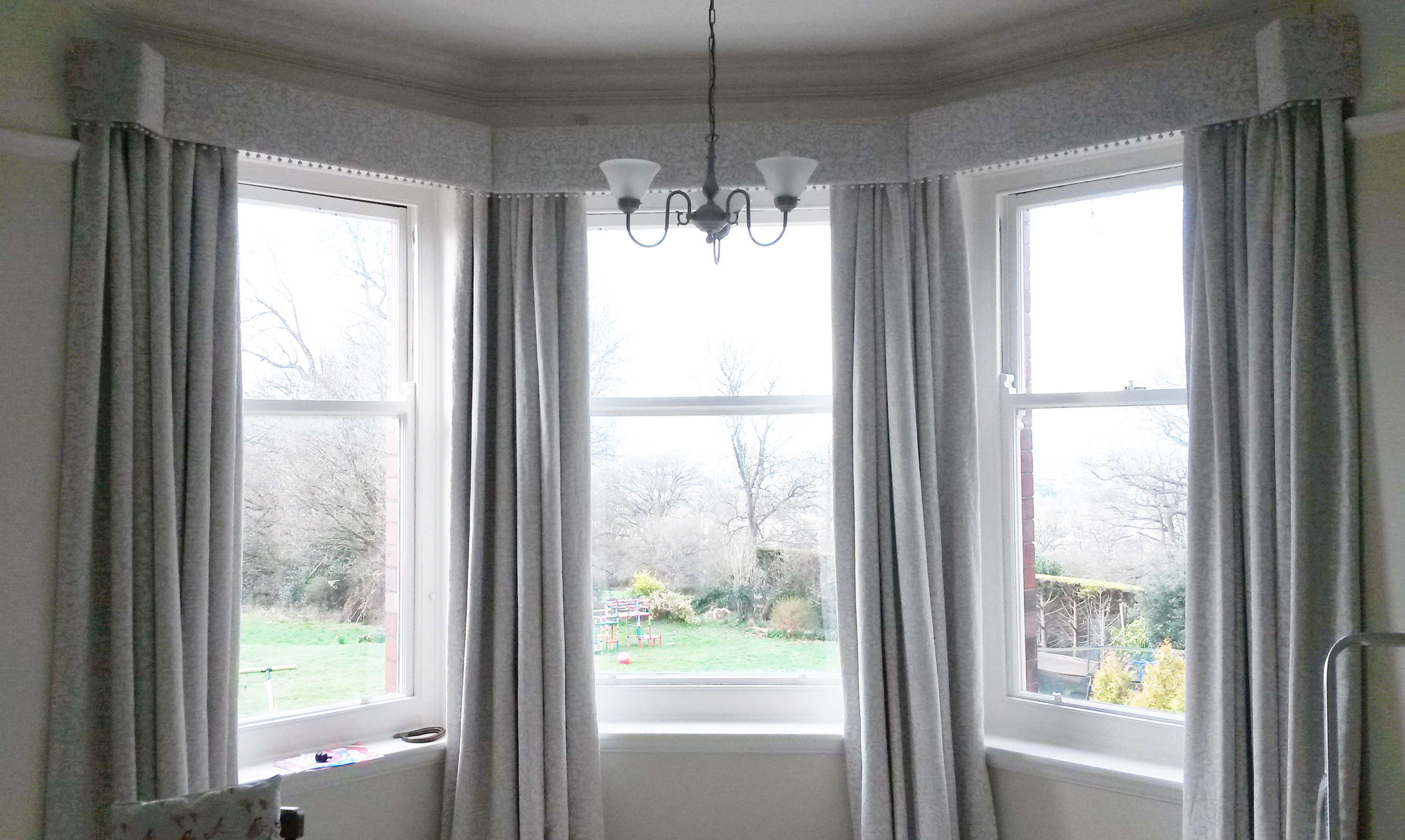 Interlined curtains in bay window with pom pom trim pelmet