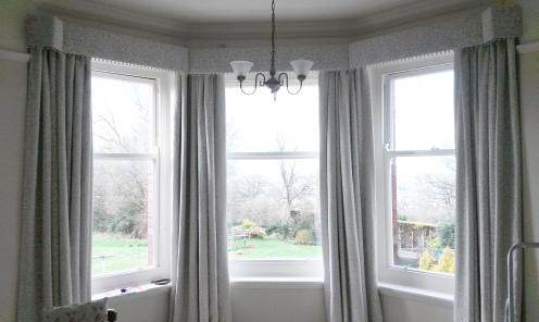Interlined curtains in bay window with pom pom trim pelmet